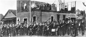 A photograph showing group of rioters posing outside the ruins of the