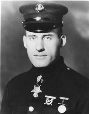 Head and shoulders of man in circa 1920 U.S. Marine dress uniform, wearing a star-shaped medal hanging from a ribbon under his collar.