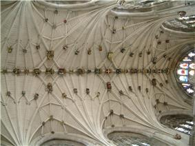 This view shows a vaulted ceiling of great complexity with many small interconnecting ribs. There are carved and gilt stone bosses wherever the ribs meet.