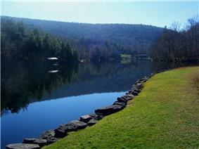 A small lake with a smooth surface reflecting the blue sky above and a hill beyond it with some buildings along the far shore. In the foreground, at lower right, the edge is marked by a stone retaining wall