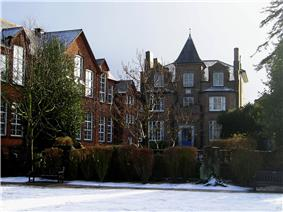 A colour photograph of an unusual Victorian house with a small spire on the top. To the left is a set of old fashioned schoolrooms with large sash windows. In front of the house is a small lawn, covered in snow.