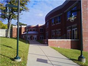 Picture of a campus building with a walkway on an autumn day
