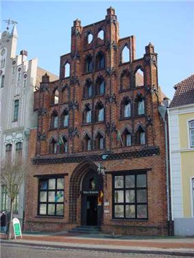 A brick building with a roof tapering dramatically toward the top via large square windows.