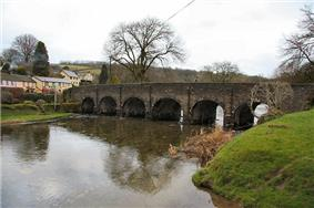 Stone bridge with six arches over water.