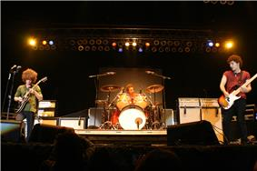 Three men on a stage in front of a crowd; two are holding guitars while the one of the center is sitting behind a drum set. Audio equipment, a drum set, lighting, and other stage fixtures can also be seen in the background.