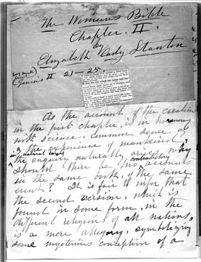 A monochrome photograph of a manuscript page, with a small clipping from a copy of the Bible pasted onto the center, and quill pen cursive writing above and below the clipping stating the name of the book-in-progress, the author, the chapter, and the beginning of the chapter text