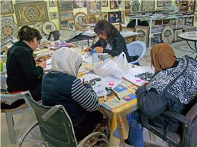 Four women, one in a wheelchair and two wearing headscarves, sitting around a table assembling mosaics with tools and materials
