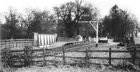 Short wooden platform on top of a bridge. A small wooden hut in the background is the only visible building.