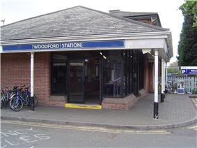 A red-bricked building with a rectangular, dark blue sign reading