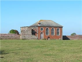A small brick Neoclassical chapel with a slate roof, and part of a loggia behind