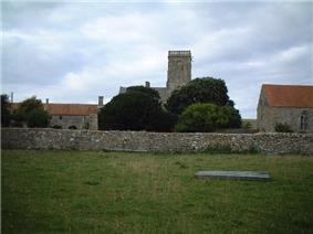 Square stone tower and red roofed buildings behind a stone wall and partially obscured by trees.