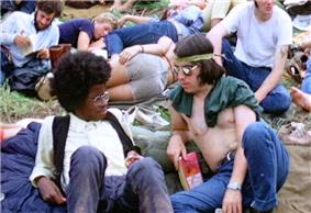 A color photograph showing people sitting on grass, in the foreground a back and a white male look at each other