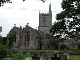 Two bay building with square tower with spirelet. In the foreground are gravestones in a grassy area.