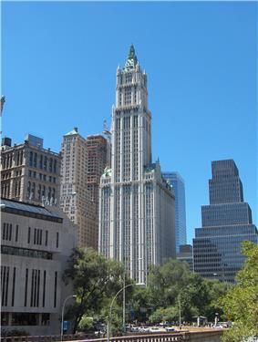 Distant ground-level view of a 60-story building; the building has setbacks on several levels and a pyramidal copper roof with several large spires.