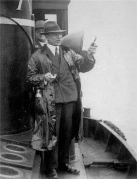 A man wearing hat and coat, gesturing with a pipe aboard a small ship