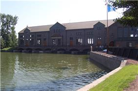 A large building stands behind a big pool of water, which enters the former through six gratings.