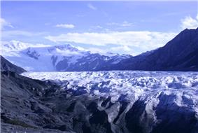 A glacier, mountains of black gravel and snowcovered mountains.