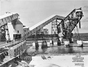 Black and white photograph of an industrial facility that juts out over a body of water. The facility appears damaged as large sections of it are sloping into the water.