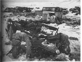 Many destroyed or damaged trucks scattered around a field. Snow and dirt cover everything.