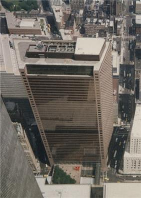 Aerial view of a skyscraper with a trapezoidal cross section and a brown glass exterior