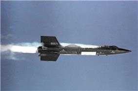 Black rocket aircraft with stubby wings and short vertical stabilizers above and below tail unit in-flight
