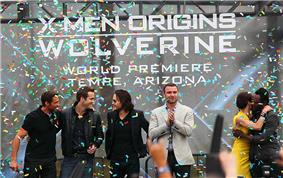 Atop a stage are three man in black clothing, Liev Schreiber wearing a gray jacket and black pants, and Lynn Collins, wearing a yellow dress, hugging will.i.am, who is in black clothing. In the background is a billboard reading