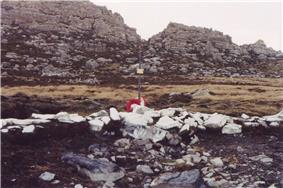 A cross amongst rocks painted white and a mountain in the background