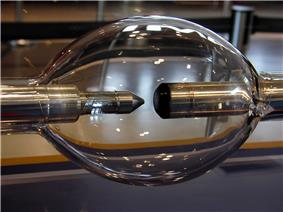Elongated glass sphere with two metal rod electrodes inside, facing each other. One electrode is blunt and another is sharpened.