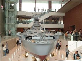 Rear view of a very large model of a battleship in an open gallery. It is surrounded by people examining the model and taking photographs of it