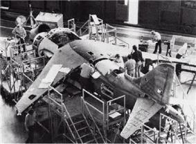 Three-quarter black and white view of a jet aircraft undergoing construction