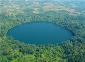 A deep blue, round lake surrounded with forest. Nearby, the forest has been replaced with fields.