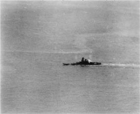A large area of ocean with a warship in the middle distance. A plume of smoke is coming from the rear of the ship's superstructure, and the ship appears to be leaning to the left.