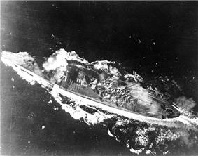 A close view of a large warship from almost directly overhead. Her wake is streaming out behind her and two trails of smoke are visible: a faint plume near her smokestack and a much thicker white plume partially obscuring her foremost main gun turret.