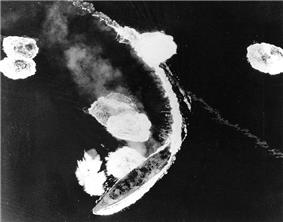 An overhead view of a large warship partway through a turn to the right. The ship's wake curves around behind her, and the surrounding sea is dotted with large areas of disturbed water and foam.