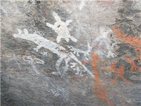 gray stone wall with white and orange primitive drawings