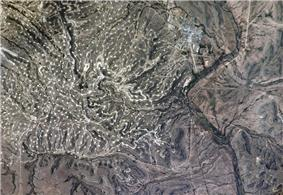 A photograph looking down on hilly, treeless terrain with a town to the upper right and the thin line of a river crossing up and down on the right
