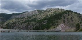 The York-Trout Creek Bridge over the Missouri River below mountains in Helena National Forest.