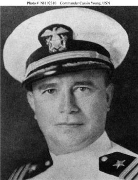 Head of middle-aged white man wearing a white jacket with black shoulderboards and a white peaked cap with a black visor.
