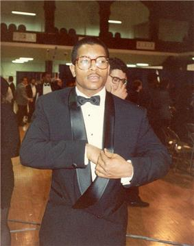 A man wearing a tuxedo and eyeglasses; other people can be seen in the background, along with folding chairs.