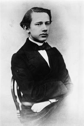 A clean-shaven man in his teens wearing a dress shirt, tie and dark jacket.