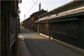 A small street lined by wooden two-storied houses.