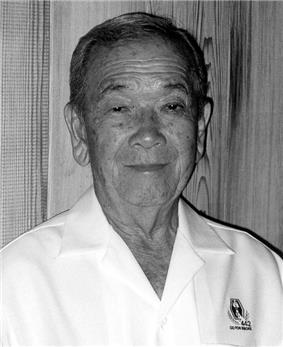 Head and shoulders of an elderly man wearing a white button shirt with an emblem on the left breast bearing the text