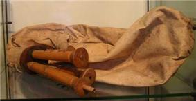 A simple bagpipe made of cloth with two wooden mouthpieces.
