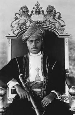 A black-and-white photograph of a man with a dark moustache wearing a turban and a dark jacket and sitting on a throne topped by two metal lions