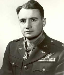 Head and shoulders of a man with wavy hair wearing a military jacket with rows of ribbon bars and a winged pin on his left breast, pins on the lapels, and a star-shaped medal hanging from a ribbon around his neck.