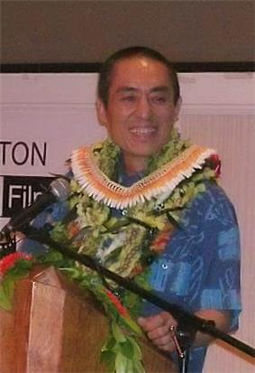 A middle-aged Chinese man standing at a podium, wearing a Hawaiian shirt and lei