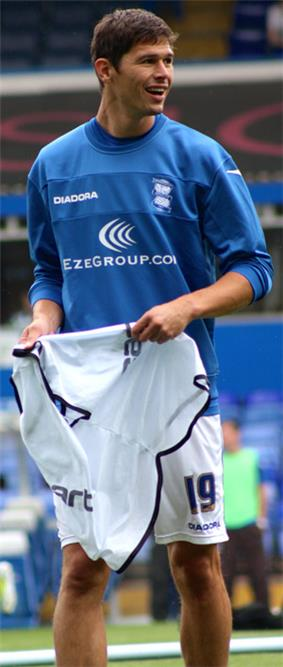 White man wearing blue and white sports training kit, pictured outdoors