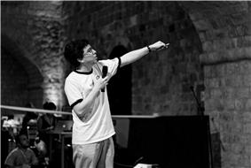 knee high portrait, speaking into a microphone and pointing in a room with an arch made of bricks in a T-shirt