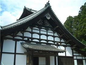 A wooden building with white walls and large gabled roof.