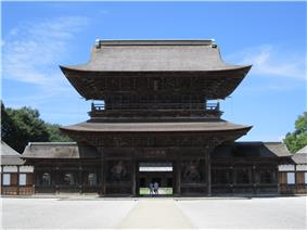 Two-storied wooden gate with a hip-and-gable roof and a passage in the central bay.